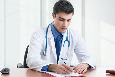 doctoring: Medico che scrive una prescrizione sulla sua scrivania