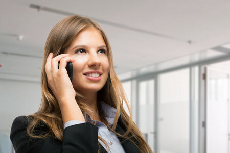 mobile voip: Young businesswoman talking on the phone
