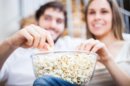 palomitas: Joven pareja comiendo palomitas de maíz mientras ve una película