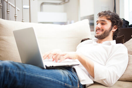 single rooms: Man using a laptop on the couch