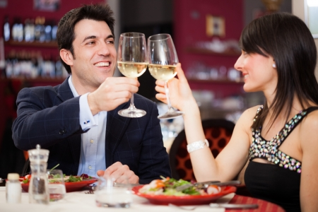 dinner date: Happy couple toasting glasses