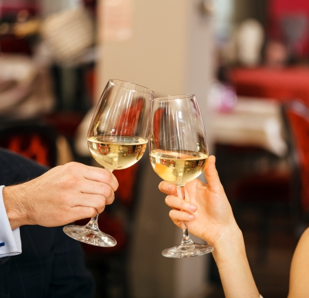 Beautiful couple toasting wineglasses in a restaurant photo