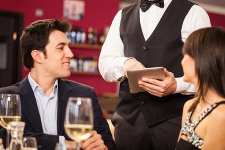 Ober die een digitale tablet om een bestelling te nemen