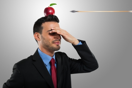 crisis management: Risk management concept, arrow hitting an apple on a businessmans head Stock Photo