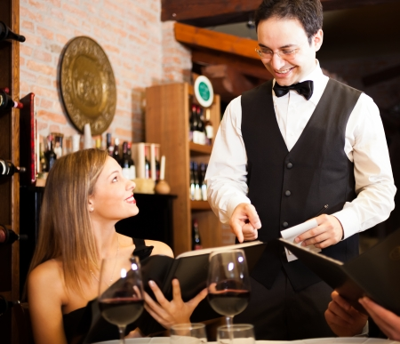 restaurant interior: Waiter suggesting food to a woman in a restaurant