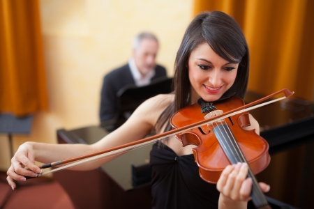 music education: Portrait of a smiling woman playing her violin Stock Photo