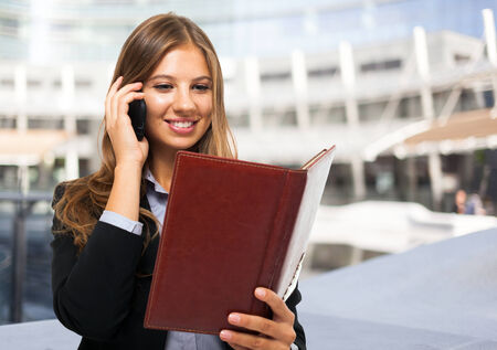 business woman phone: Young businesswoman reading her agenda