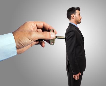 Hand winding up a mechanical businessman photo