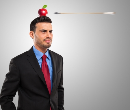 hedging: Risk management concept, arrow hitting an apple on a businessmans head Stock Photo