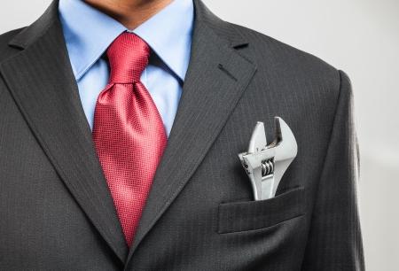 彼のポケットでモンキー レンチを維持するビジネスマン