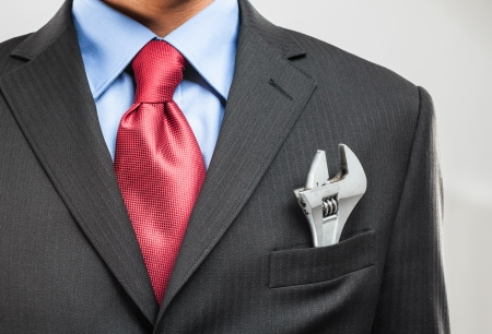 Businessman keeping an adjustable wrench in his pocket