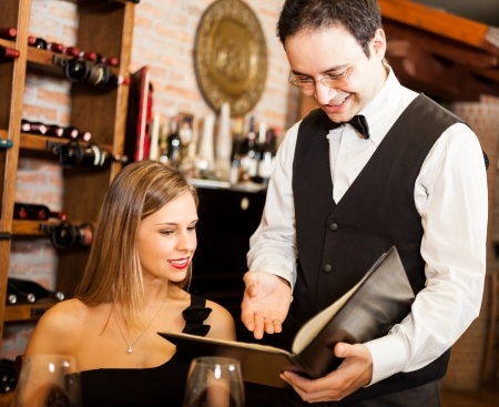 Waiter suggesting food to a woman in a restaurant photo