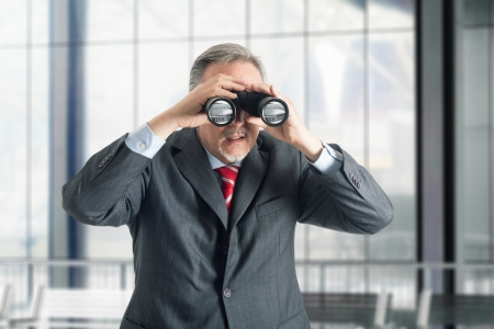 Businessman watching through binoculars photo