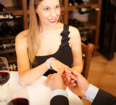 Man giving a ring to his girlfriend in a restaurant photo