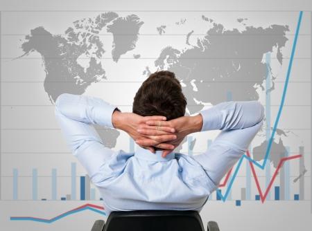 empresas: El hombre de negocios se relaja en su silla mientras el negocio crece