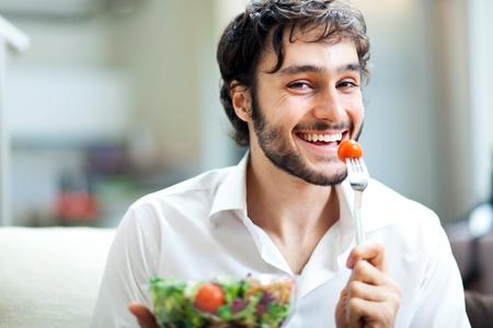 uomo felice: Giovane uomo mangiare insalata Archivio Fotografico