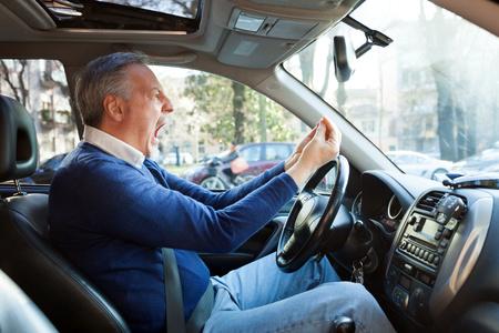 Portret van een boze chauffeur schreeuwen in zijn auto