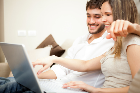 Couple using a laptop computer on the couch photo