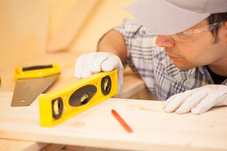 bubble level: Portrait of a carpenter using a bubble level Stock Photo