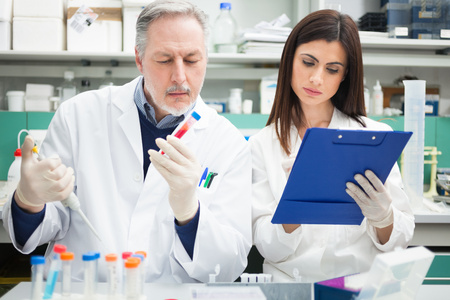scientist woman: Two scientists at work in a laboratory