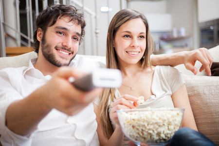 sofa television: Young couple preparing to watch a movie