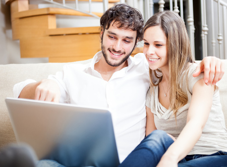 internet love: Young couple using a laptop computer
