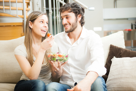 Couple eating a salad on the couch photo