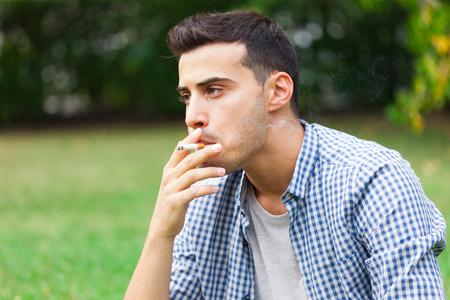 joven fumando: Hombre que fuma un cigarrillo al aire libre