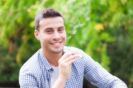 joven fumando: Hombre que fuma un cigarrillo electrónico aire libre
