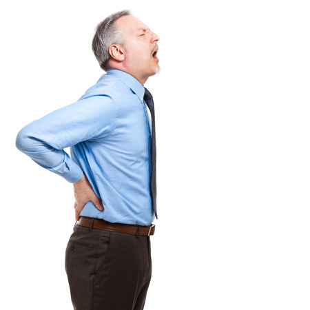 back strain: Man struggles with intense back pain on white background