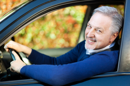 Mature man driving his car photo