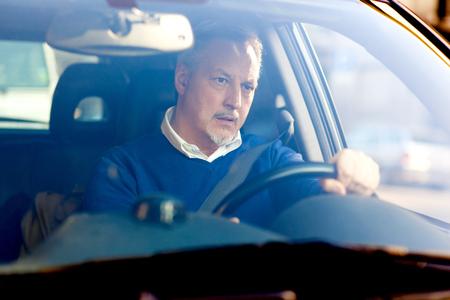 Bored mature man driving his car photo