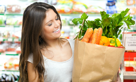 Young woman holding a shopping bag full of vegetables photo