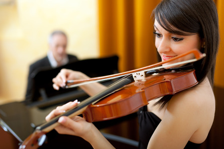 Female violinist and male pianist playing together photo