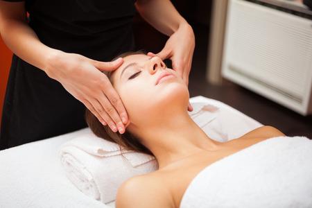 tratamiento facial: Mujer hermosa que tiene un masaje facial Foto de archivo