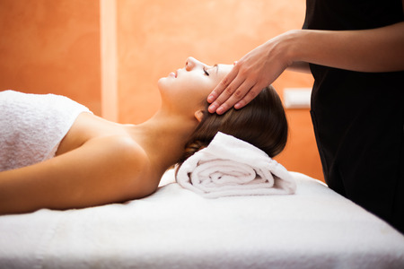 Massage therapy: Beautiful woman receiving a facial massage Stock Photo