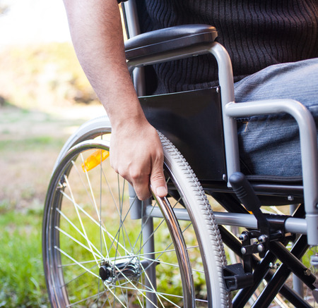 handicapped person: Paralyzed man using his wheelchair Stock Photo