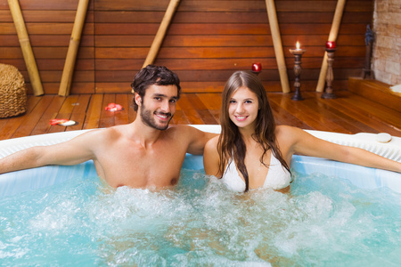 Smiling couple relaxing in a whirlpool photo