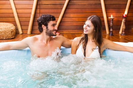 resort life: Happy couple relaxing in a hot tub Stock Photo