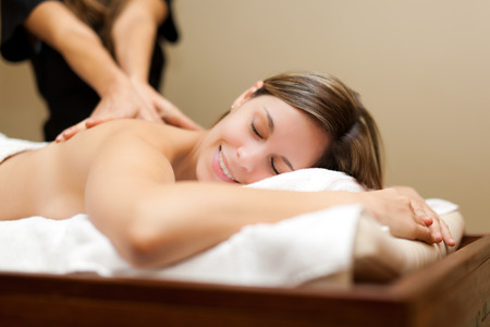 massage face: Young woman receiving a massage in a spa
