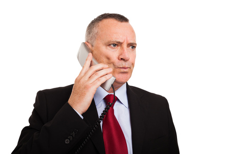 opting: Portrait of a puzzled businessman talking on the phone