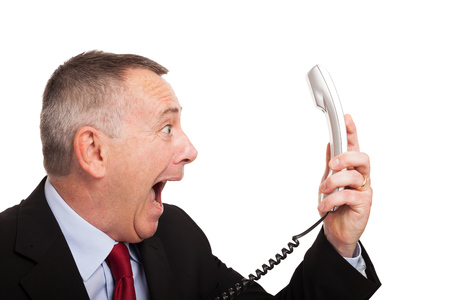 Portrait of an angry businessman yelling at phone photo