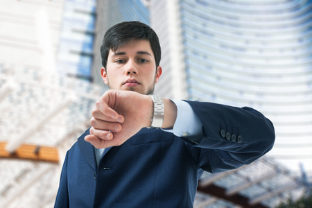 checking the time: Young businessman looking at his watch