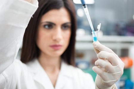 in vitro: Científico poniendo una muestra en un tubo de ensayo en un laboratorio de química