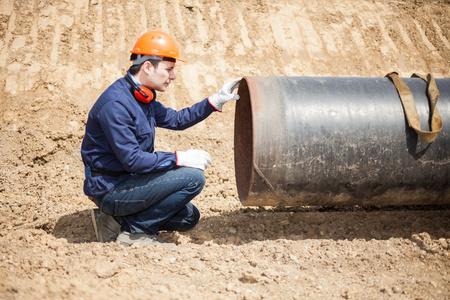 工事現場でパイプを調べる男 写真素材