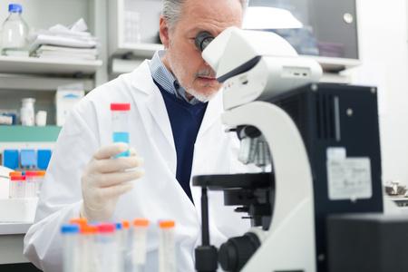 in vitro: Hombre que usa un microscopio en un laboratorio de química Foto de archivo