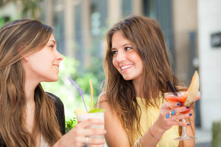 two women talking: Portrait of two friends drinking a cocktail Stock Photo