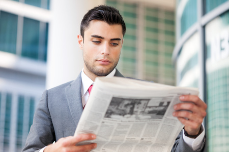 Portrait of a young business man reading a newspaper photo