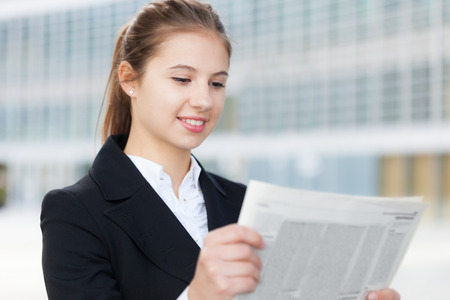 classified ad: Portrait of a young business woman reading a newspaper Stock Photo