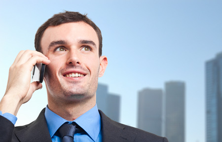 Young businessman talking at the phone outdoor photo